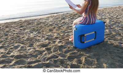 Young woman is painting on the beach