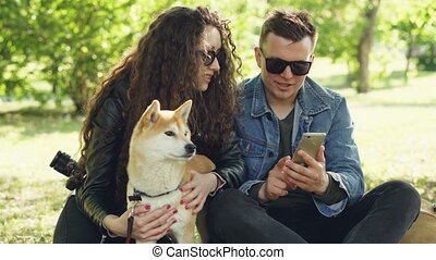 Young woman is petting her dog sitting on grass while her...