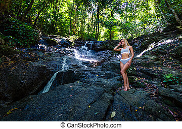 Young woman is posing at small waterfall