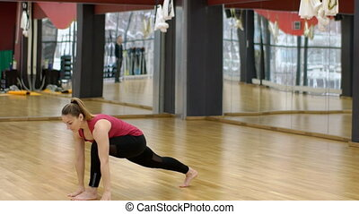 Young woman is practicing yoga in modern studio indoors.