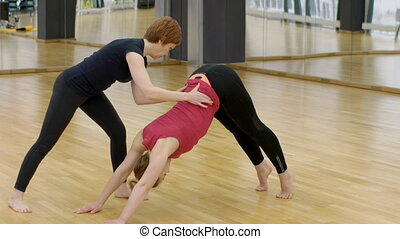 Young woman is practicing yoga with instructor in modern...