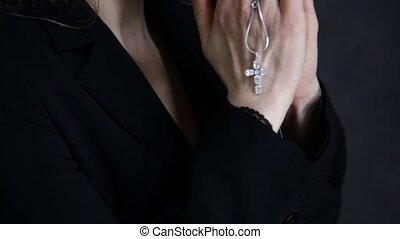 young woman is praying. close-up female hands holding chain with a cross