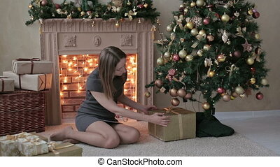 Young woman is putting gifts under Christmas tree