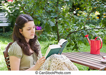 Young woman is reading in a garden