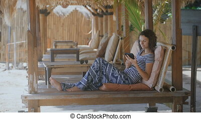 Young woman dressed in casual clothing is relaxing in hot summer day, lying on sunlounger under the tent and using her tablet. Attractive brunette is enjoying her exotic vacation having rest in rush marquee alone with her pocket book.