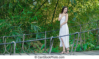 Young woman is relaxing on the hanging bridge