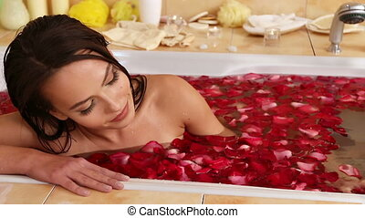 Young woman is relaxing with rose petals bath in spa salon....