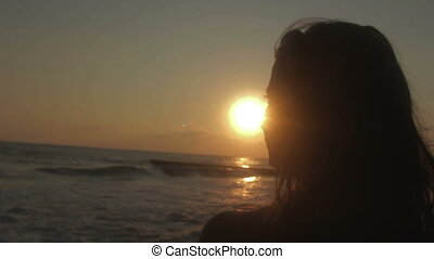 Young woman is seeing at sea and sunset.
