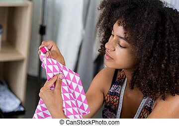 young woman is sewing with a needle