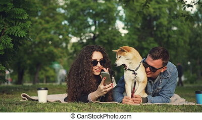 Young woman is showing funny pictures on smartphone to her...