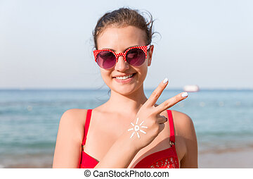 Young woman is showing peace gesture and has sun shape on her hand at the beach