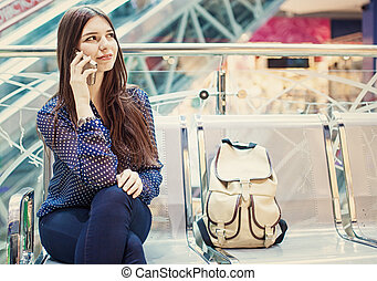 Young woman is sitting at an airport and speaking by her phone.