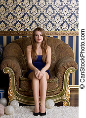 young woman is sitting in old chair.