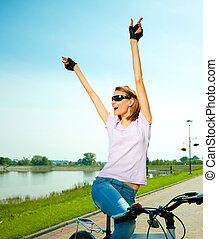 Young woman is sitting on her bicycle