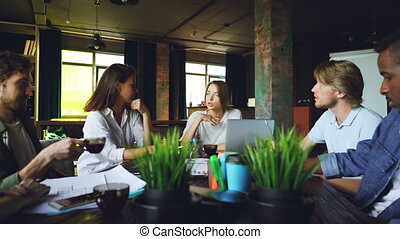 Young woman is speaking with colleagues sitting at table in office discussing work plans while her team is listening to her, male coworker is drinking tea.