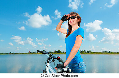 Young woman is standing behind of her bicycle