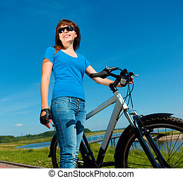Young woman is standing in front of her bicycle