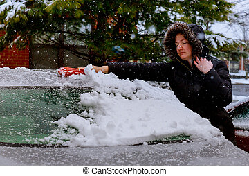 Young woman is sweeping off snow from her car - Woman...