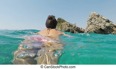 young woman is swimming in the Adriatic Sea, Montenegro.