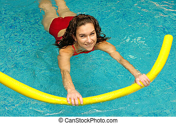 young woman is swimming with noodle