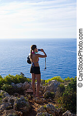 Young woman is taking photos - Keri, Zakynthos, Greece -...