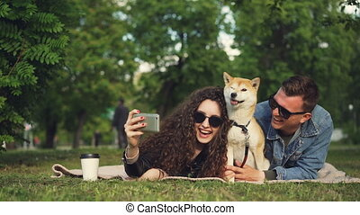 Young woman is taking selfie in the park lying on grass with her boyfriend and pet dog, adorable animal is sneezing and licking its nose, people are laughing.