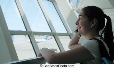 Young woman is talking on mobile phone in airport terminal in flight zone.