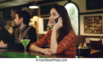 Young woman is talking on mobile phone while sitting at counter in bar with cocktail. Customers moving and talking in background. Modern communication in pub concept.