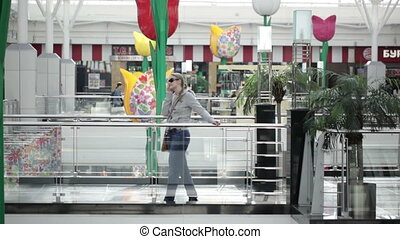 Young woman is talking on the mobile phone in shopping center.