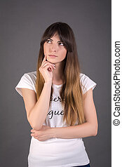 Young woman is thinking about something. Female on a gray background.