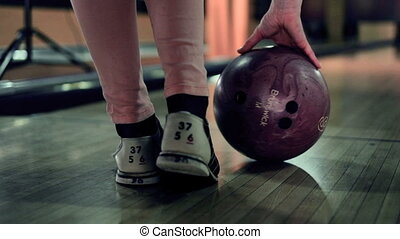 Young woman is throwing ball in a bowling club Slow motion