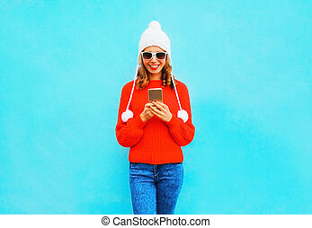 Young woman is using smartphone in red sweater, hat on a blue background