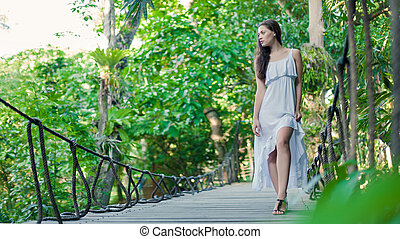 Young woman is walking on the hanging bridge