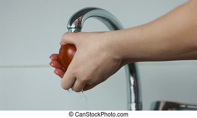 Young woman is washing a tomato in the kitchen, closeup footage.