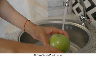Young woman is washing green apple under tap in home...