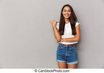 Young woman isolated over grey background pointing to copyspace.