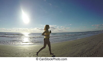 Young woman jogging along the sea on sandy wet beach