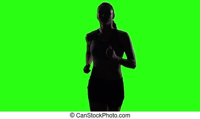Young woman jogging in a medium frontal shot. Green screen. Slow motion