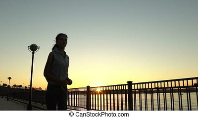 Young woman jogging in sunset - SLOW MOTION: Young woman...