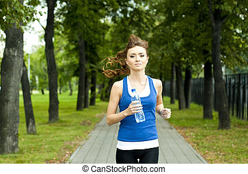 young woman jogging in the park in summer, trees and grass...