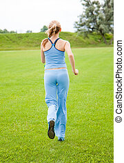 young woman jogging in the park in summer - A young woman...