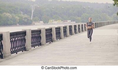 Young woman jogging on city embankment while morning...