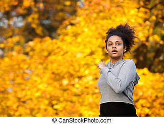 Young woman jogging outdoors in autumn