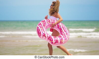 Young woman jogging with Inflatable donut, with Inflatable...