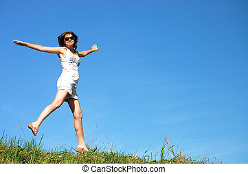 young woman jumping against the beautiful sky