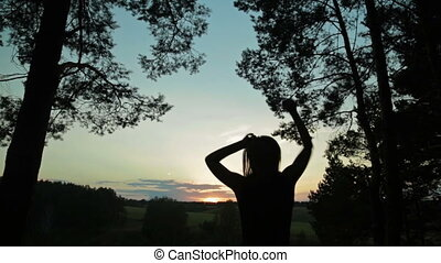 Young woman jumping and dancing in the forest after sunset