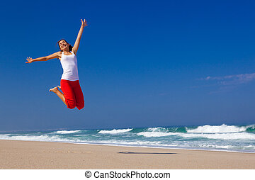 Young woman jumping - Beautiful young woman jumping on the ...