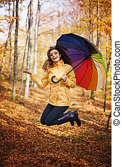 Young woman jumping during the rainy day at autumn