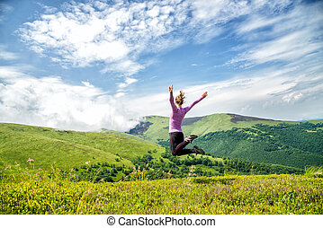 Young woman jumping in the mountains