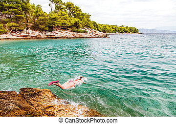 Young woman jumping in the water